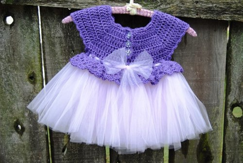 This one will be going to Cyprus, Texas to Debby for her granddaughter who will be one in August. Debby was the first one who ordered one of my tutus. Silly me, I didn't ask her for any measurements of her little granddaughter and assumed that the one that I had made would fit her. Well....the tutu was too small so this time I asked her for measurements and I am hoping that this one will work for her. Of course the true color of purple is actually darker than the picture shows here and the lavender tulle and sparkly purple buttons are more beautiful in person. Anyway, this little dress will be making its way to Texas real soon.
