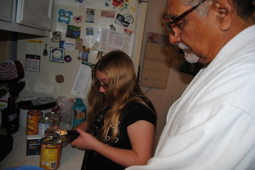 John enjoys teaching Megan, even when he acts like he doesn't. Here, he is teaching her how to operate a manual can opener.