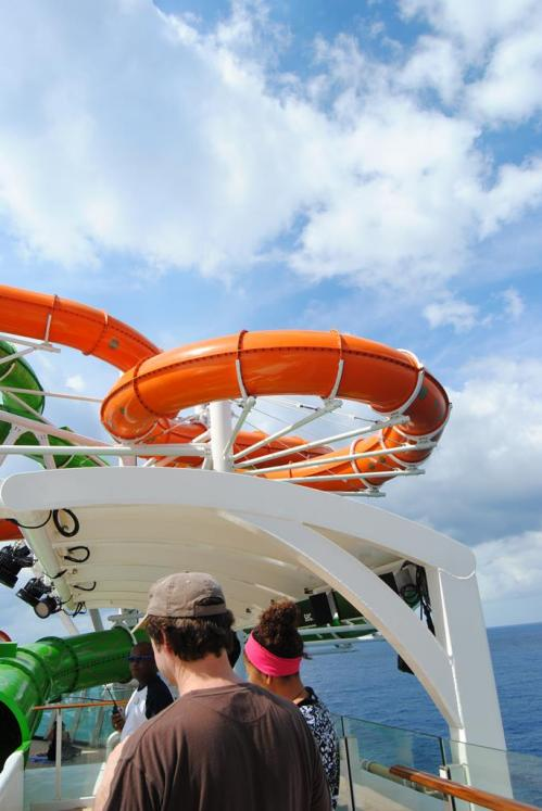 The orange slide is sticking way out over the edge of the ship.